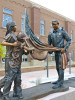 Legacy of Service, 2 children and police officer raising flag, by sculptor Greg Todd