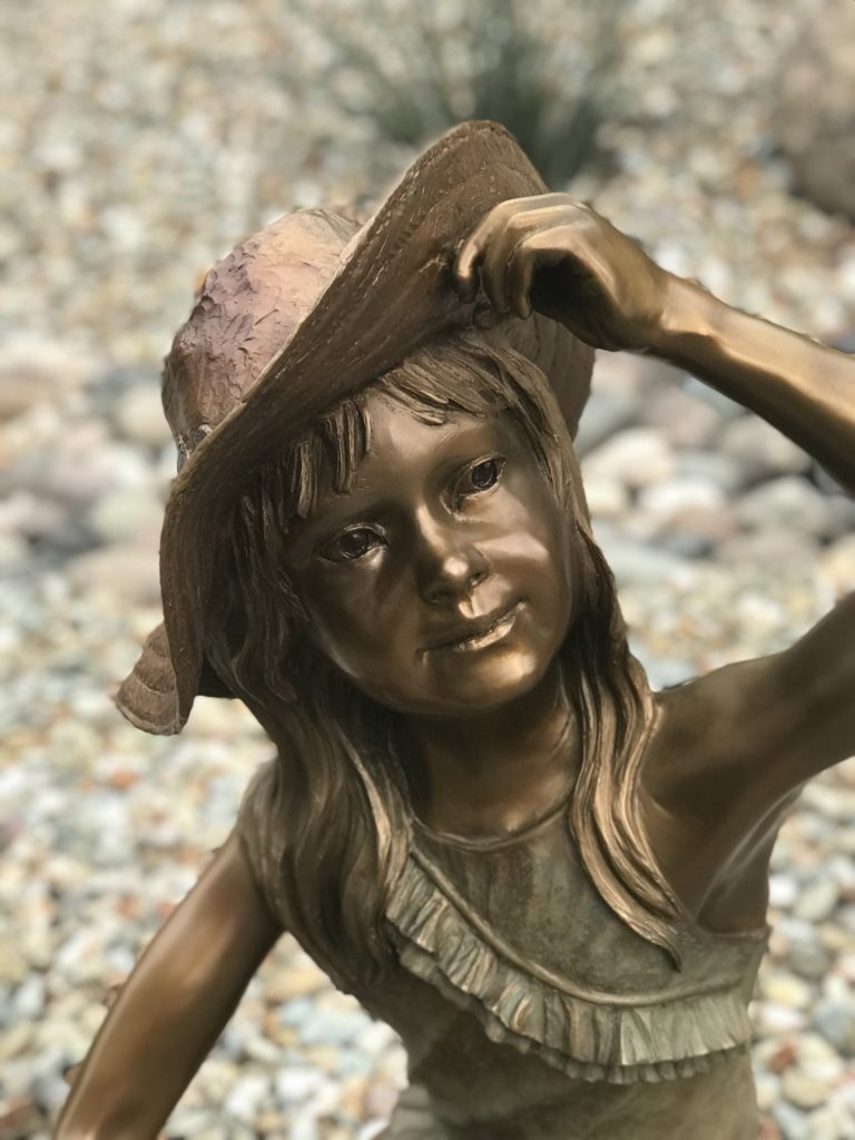 young girl wearing floppy brimmed hat looks up as she is building her sand castle