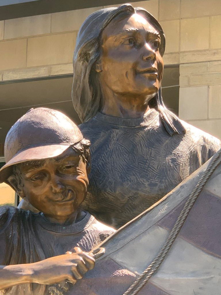 Legacy bronze sculpture by Colorado artist Greg Todd detail of faces of boy and girl